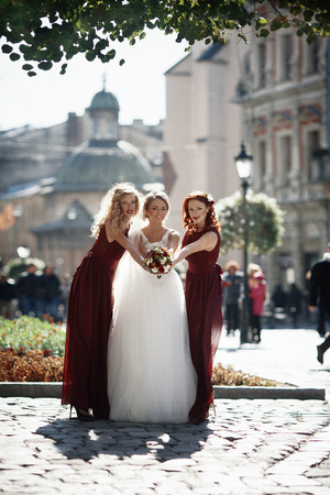 The bridesmaids with bride stand in the center of town Stock Photo