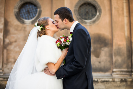The charming couple in love kissing  near building