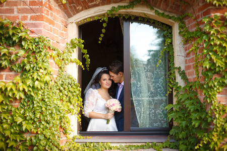 Stunning wedding couple stands in the window of an old brich house