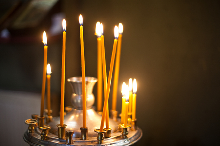 candleholder: High yellow candles stand on the steel candleholder in church Stock Photo