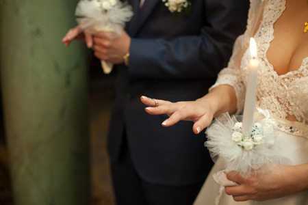 Bride and groom hold wedding rings on their fingers during the ceremony Stock Photo