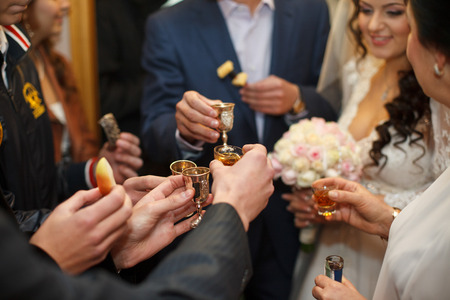 clang: A closeup of guests hands while they clang glasses with newlyweds