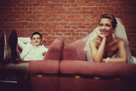 couches: Happy newlyweds rest on the red couches Stock Photo
