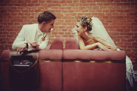 couches: Bride and groom smile to each other sitting on the different couches Stock Photo