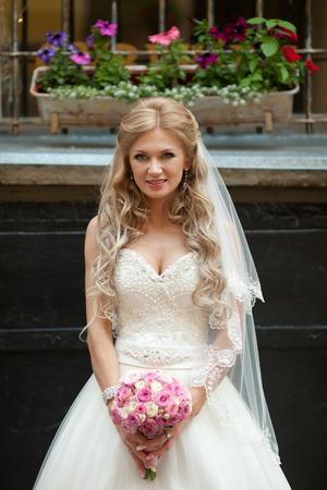 Tiny blonde bride stands under the windowsill full of flowers Reklamní fotografie