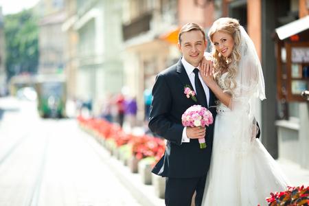 Happy bride leans on groom's shoulder standing between flowerpots on the street Reklamní fotografie