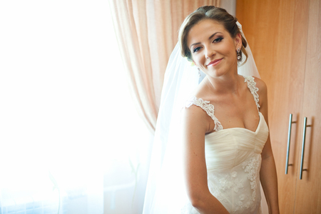 Pretty thin bride looks over her shoulder standing behind a window