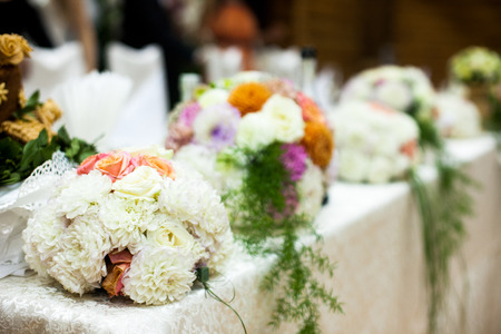 Wedding table decorated with white boquuets and greenery