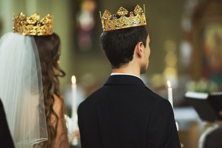 Bride and groom stand in the crowns before a priest during an engagement ceremony
