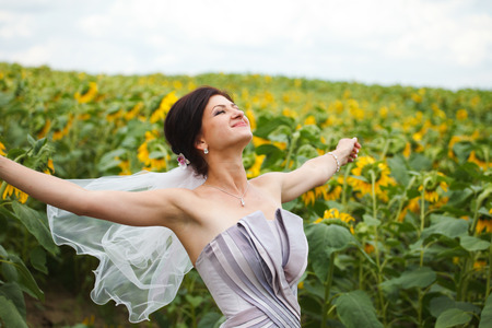 Bride in violet dress enjoys a moment standing on the field Stock Photo