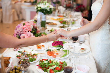 Bride hodls womans hand over the dinner table