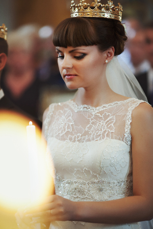 christian marriage: Thoughtful bride in an engagement crown looks on the burning candle Stock Photo