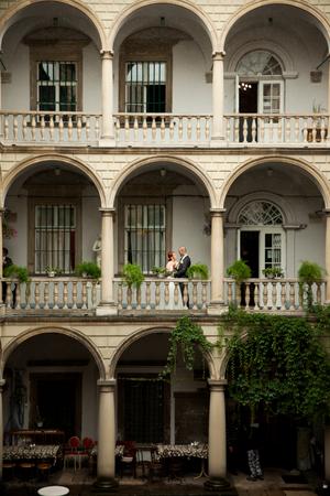 bilding: A look from a far on the wedding couple posing on the Italian balcony
