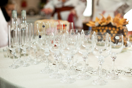 Empty wineglasses stand on the white dinner table Stock Photo