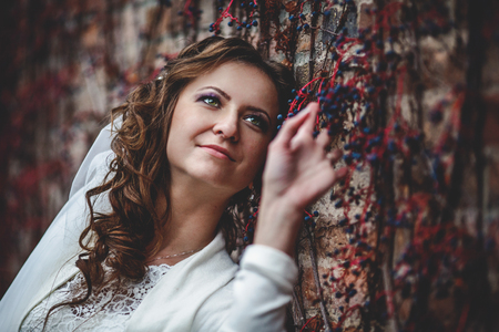 Bride leans to a brick wall covered with blue berries Stock Photo