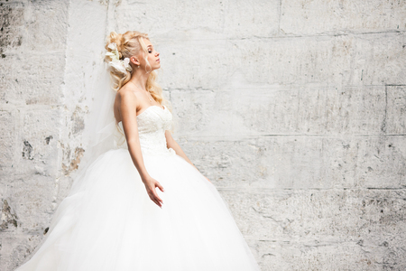 spreads: Curly blonde bride spreads her hands standing behind a white wall Stock Photo