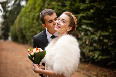 fiance: Groom kisses a delicate bride in a cheek while posing in the park