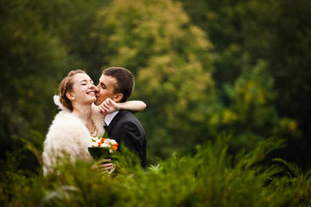 Bride hugs grooms neck while he kisses her cheek