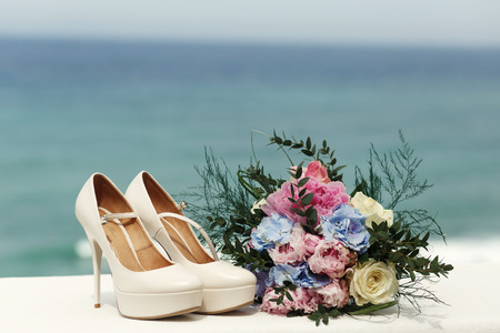Gorgeous bouquet stands before the classy wedding shoes Stock Photo