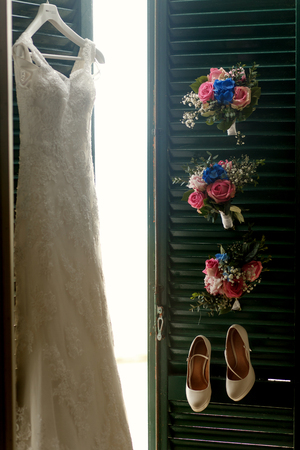 Sun shines through the green doors on which hang dress, shoes and bouquets