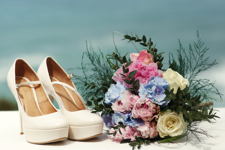 Pastel wedding bouquet of pink and blue peonies stands behind the shoes