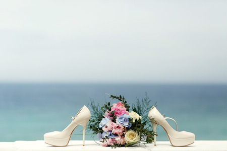 White shoes stand on different side of wedding bouquet