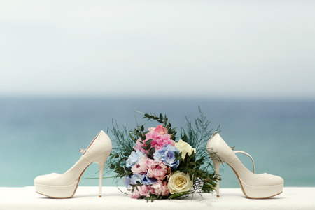 White wedding shoes and rich bouquet stand on the white table with great view on the sea behind them Stock Photo