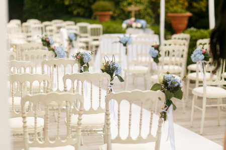 romantic places: Delciat bouquets of white hydrangeas pinned to the chairs Stock Photo