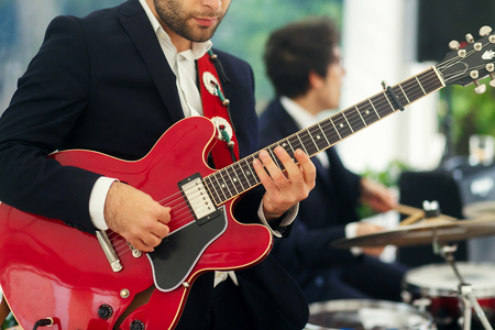 Man in black suit plays red guitar standing with a band