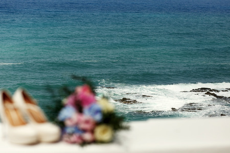 Sea splashes over the rocks behind the blacony with wedding shoes and a bouquet Stock Photo