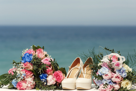 Delicate beige wedding shoes stand between gorgeous bouquets in the front of great landscape Stock Photo