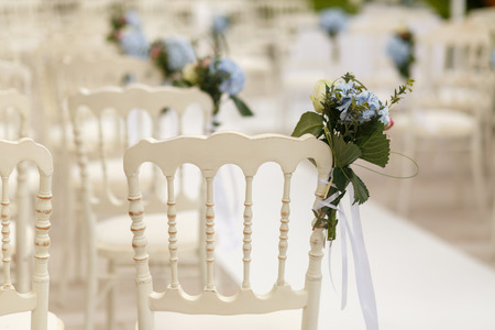 Bouquets of greenery and blue hydrangeas pinned to the white chairs