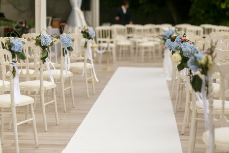 romantic places: White path runs between the chairs decorated with blue flowers Stock Photo