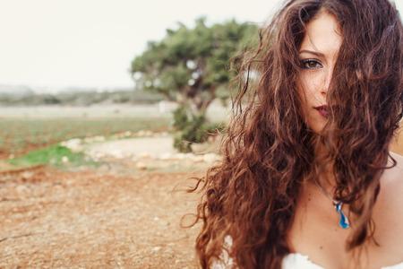 Dreamy woman with dark lips looks through the beautiful curls Standard-Bild