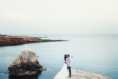 spreads: Azure sea spreads around a wedding couple hugging on the rock Stock Photo