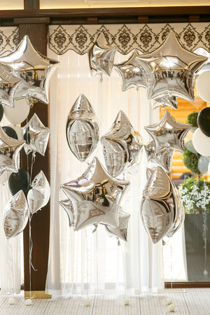 Silver baloons hang under brown ceiling Stock Photo