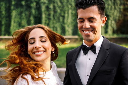 Groom laughs and closes his eyes while bride whirls her hair standing behind him