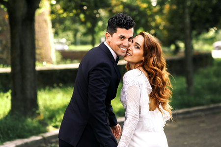 Curly bride leans to groom's cheek while posing in the park