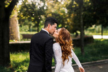 Curly bride leans to a groom for kiss while they walk in the park