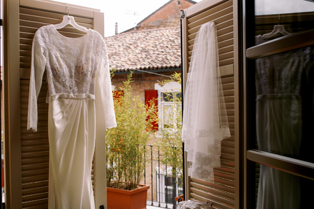 Wedding gown hangs on the wooden doors to the balcony Stock Photo