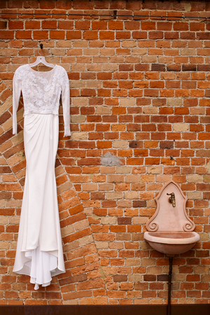 Classy wedding dress hangs on the brick wall
