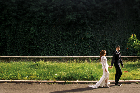 Groom and bride in elegant dress walk along the path in the park Stockfoto