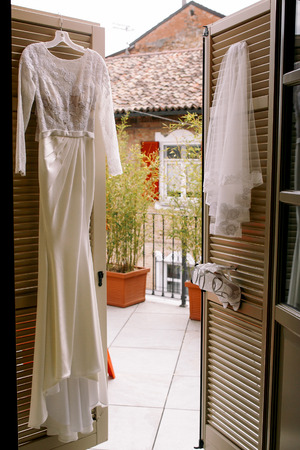 Elegant wedding gown and veil hang on the doors to the balcony