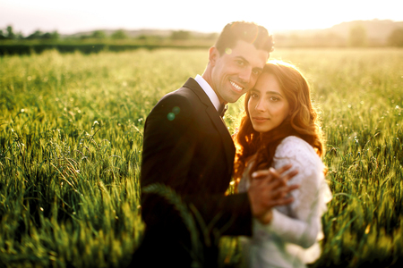 Groom holds brides hand while posing in the lights of evening sun