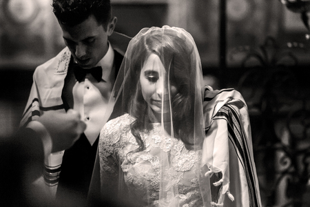 Jewish wedding. Black and white picture of groom covering with his shawl bride's shoulders Archivio Fotografico