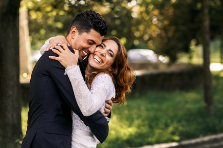 Bride and groom hug each other tightly while laughing in the park