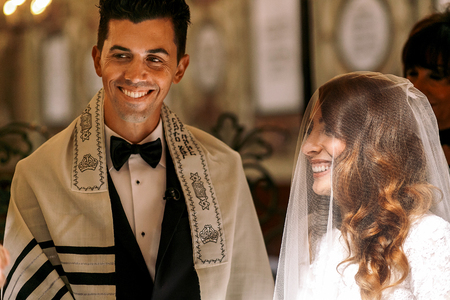 Jewish wedding. Beautiful bride looks at a groom