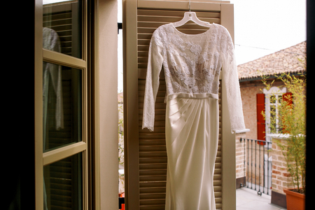 White lace wedding gown hangs on the wooden door Stock Photo