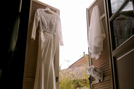 Wedding dress, veil and shoes hang on the light wooden doors
