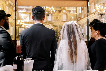 Look from behind at Jewish newlyweds standing in the synagogue